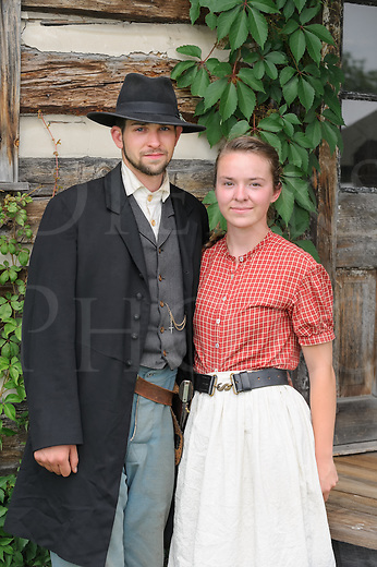 Man and woman from the 1880's American Wild West standing in front of log cabin house, a couple in their twenties in reenactor portrayal.