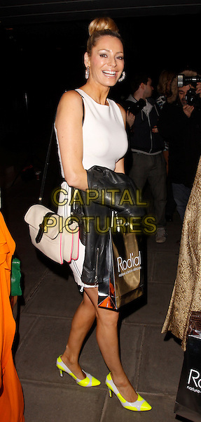 Tess Daly.Rodial Beautiful Awards, Sanderson Hotel, London, England..March 6th, 2012.full length black leather jacket white dress yellow neon fluorescent shoes beige bag purse side.CAP/AH.©Adam Houghton/Capital Pictures.