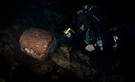 Archaeologist Guillermo de Anda inspects a carved stone column among the debris of a collapsed alter at the bottom of a cenote.