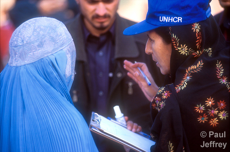 A UN worker checks who gets on the buses taking Afghan refugees from the camp at Jalozai to a new camp close to the border with Afghanistan..