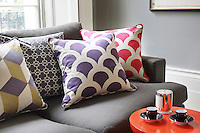 Cushions covered in a scalloped pattern in purple and pink sit beside others covered with a cube print and a Moorish inspired repeating design