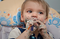 Young boy at a birthday party covered with cake holding a plastic spoon.