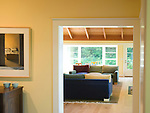 view through a wide doorway of the center hall into the bright natural-light living room (LR) of a waterfront weekend vacation retreat on Washington State's Vashon Island