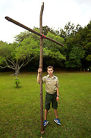 A Boy Scout shows off a temporary cross lashed together for a worship service held at Huntington Beach State Park.