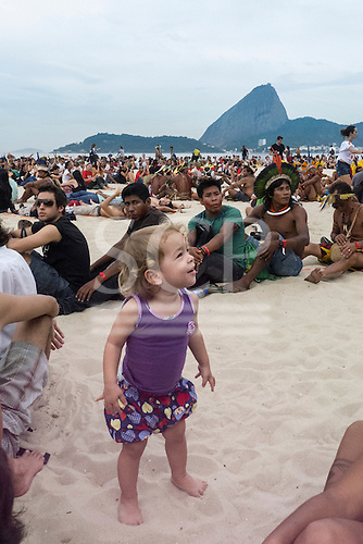 One of the youngest participants smiles at another as indigenous people form a human banner on Flamengo Beach to protest agains the construction of hydroelectric dams in Brazil with the Sugarloaf in the background. United Nations Conference on Sustainable Development (Rio+20), Rio de Janeiro, Brazil, 18th June 2012. Photo © Patrick Cunningham.