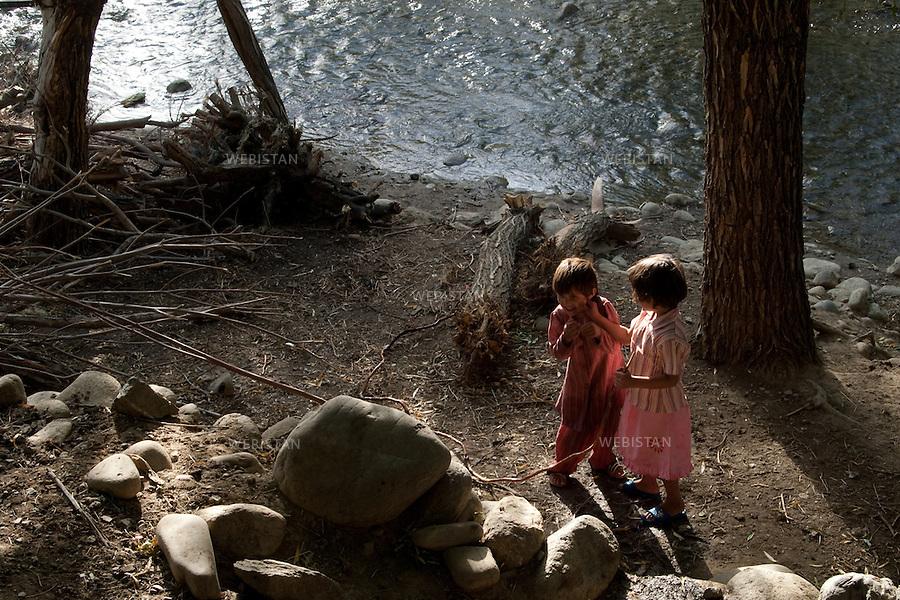 AFGHANISTAN - VALLEE DU PANJSHIR - 12 aout 2009 : Environs de Astanah, enfants jouant sur les bords de la riviere du Panjshir...AFGHANISTAN - PANJSHIR VALLEY - August 12th, 2009 : Near Astanah. Children playing on the edge of the Panjshir River.