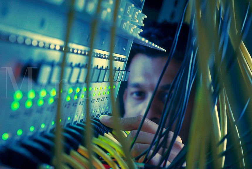Computer engineer checking wires on digital bridge