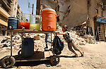 Fouad, a 11-year-old Syrian boy, pushes his juice cart, in a street in a rebel-controlled area of Aleppo, on August 8, 2015. Fouad works everyday following the school time to provide for his small family, as his father suffers from disease. Children in the country were now contributing to the family income in more than three quarters of Syrian households, according the report released by UNICEF, estimates that one in ten Syrian refugee children in the region is engaged in child labour. Photo by Ameer al-Halbi