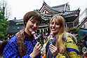 Visitors eat phallus-shaped candies during the Kanamara Festival in Kawasaki on April 3, 2016, Kanagawa, Japan. The Kanamara Matsuri or Festival of the Steel Phallus is held on the first Sunday of April at the Kanayama shrine. The shrine celebrates a legend of a steel penis and was frequented by prostitutes who wished to pray for protection from sexually transmitted diseases. Visitors now wish for easy delivery, marriage and matrimonial harmony. Because of the large steel phallus the unusual festival has become a tourist attraction attracting many overseas visitors and is used to raise money for HIV charities. Phallus shaped candy, carved vegetables, decorations, and a big parade are all part of the festival. (Photo by Rodrigo Reyes Marin/AFLO)