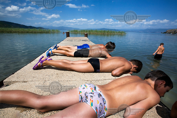 Boys sun bathing by Lake Ohrid, which is home to many rare fish species and is a UNESCO World Heritage Site..