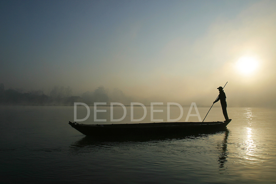 A man pushes his wooden boat across the Rapti River, which is the boundary of the Royal Chitwan National Park near the village of Sauraha, Nepal.
