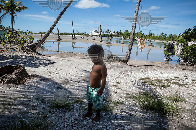 A child stands near an area of flooded ground where football is played when it is dry, at low tide, but the land is slowly being eroded and salinated by the regular flooding that occurs during high tides. Abaiang is one of Kiribati's atolls that is most threatened by rising sea levels. The country's government says Tebunginako is a 'barometer for what Kiribati can expect in the future'. Since the 1970s the village's residents have seen the sea levels rise and eventually erosion has meant that a major part of the village has had to be abandoned.