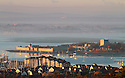 30/10/12 ..The dawn sunlight reflects off Portchester Castle, Hampshire, and turns the autumn mist pink looking across the The Solent towards the Isle of Wight. ..All Rights Reserved - F Stop Press.  www.fstoppress.com. Tel: +44 (0)1335 300098.