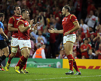 Pictured: Cory Allen of Wales (R) celebrates his try with team mates L-R Sam Warburton and Gareth Davies  just before the end of the first half Sunday 20 September 2015<br />