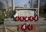 War memorial with red poppies and wreaths, Snape, Suffolk, England