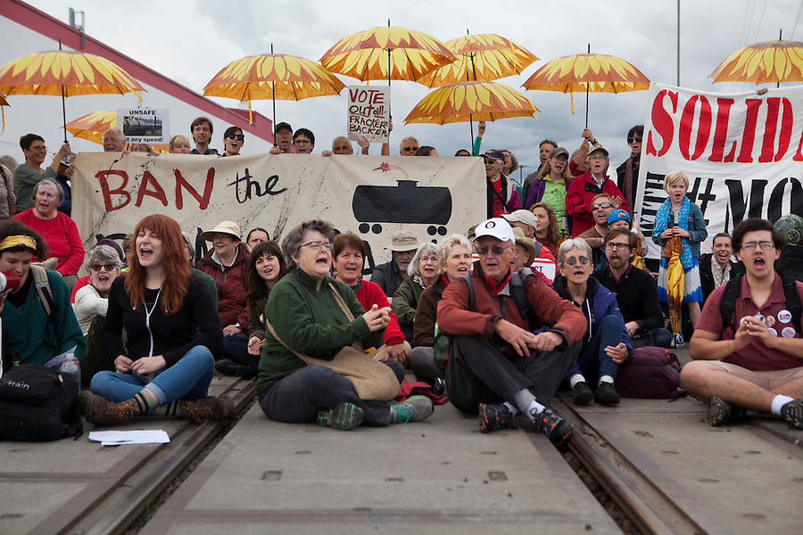 People sit on a railway tracks, singing songs and chanting slogans as they take part in a demonstration that saw BNSF rail tracks blocked by protesters in Vancouver Saturday June 18 2016. (Photo by Natalie Behring for the Columbian)