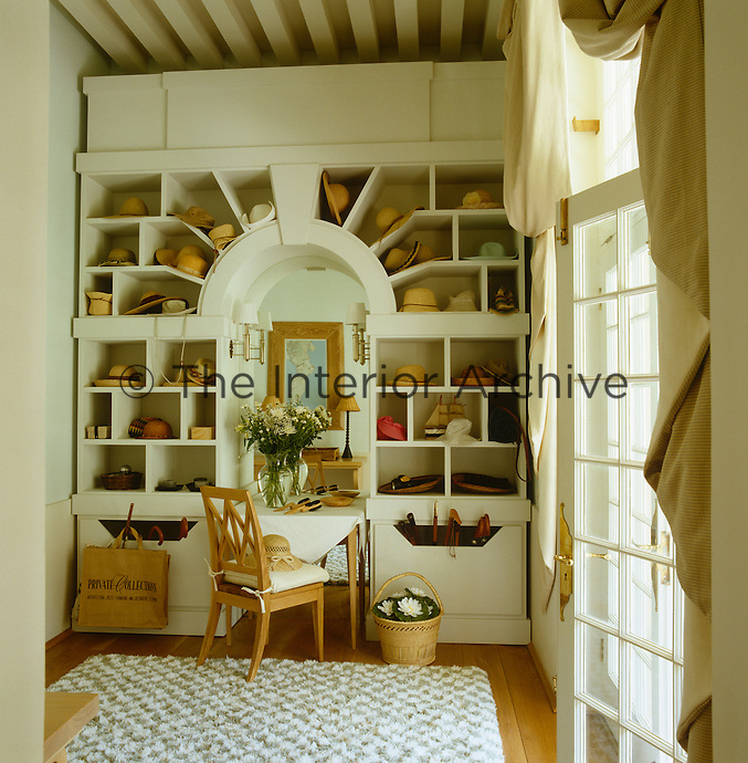 The 'hat room' is dominated by a large cabinet based on a Roman triumphal arch and the open shelves are filled with an assortment of straw hats and bowls