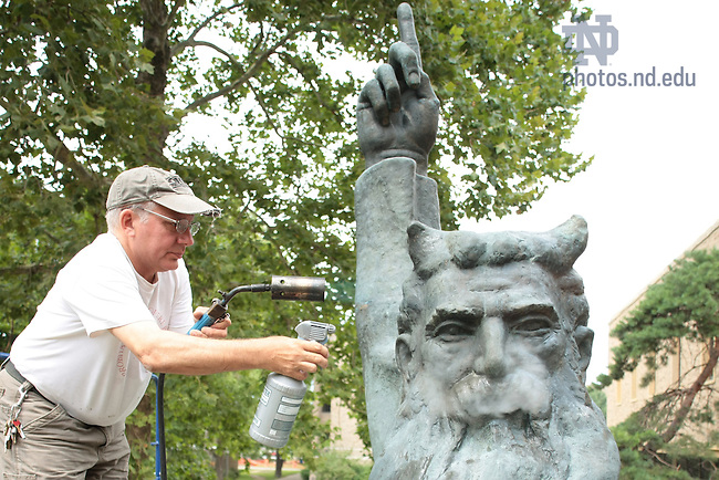 Thomas J. Podnar applies potassium sulfite and heat to the Moses statue outside Hesburgh Library as part of work to preserve and refurbish the statue.