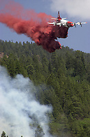 A slurry tanker drops a load of fire retardant on open flames shortly after the Missionary Ridge Fire started on June 6, 2002, north of Durango, Colorado.