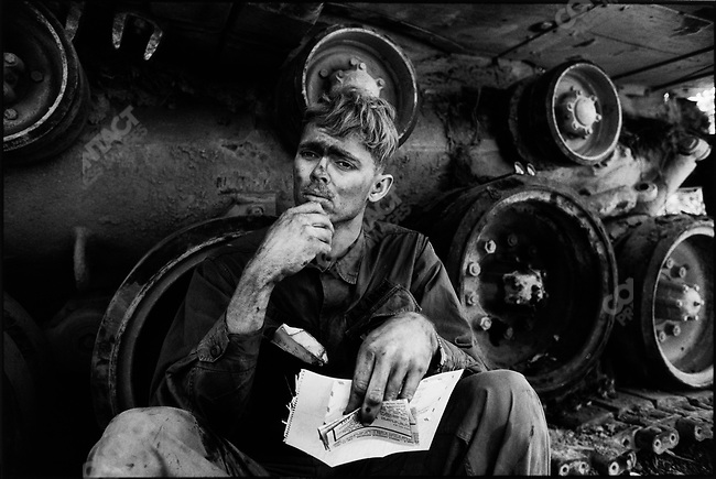 An American soldier reads a letter from home, while taking a break from repairing a tank tread. Lang Vei, South Vietnam, March 1971