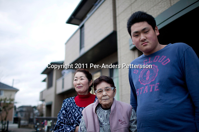 ISHIONAMAKI, JAPAN - DECEMBER 5: Student Atsushi Murata, age 17,  with his grandmother and mother outside the temporary housing block where he lives with his grandmother, mother and brother on December 5, 2011, in Ishionamaki, Japan. He is a tsunami survivor and the rescued and carried his grandmother to safety when the tsunami hit. Save The Children Japan gives out scholarships to families and assists children who's lives were disrupted and devastated by tsunami. Many children lost parents, family members and where traumatized during the tsunami. These so called Gakudos are supported by the ngo. Northeastern Japan's coastline was struck by an earthquake measuring 9.0 on the Richter scale and a Tsunami on March 11, 2011 which destroyed villages and livelihoods for hundreds of thousands of people. Almost 16,000 dead, thousands missing, more than 700,000 properties destroyed and an estimated 387,000 survivors lost their homes. Its estimated that it will take more than five years to rebuild. The cost is estimated to 309 billion U.S. dollars, the world's most expensive natural disaster. Many children suffered especially with school destroyed, education interrupted and the loss of family members took a heavy toll. Save The Children Japan runs many programs to assist families and children in the tsunami stricken areas. one of the few ngo's working here they assist with food, hygiene products, shelter, counseling, and many after school and pre school programs and scholarships for families who lost their livelihood after the tsunami. (Photo by Per-Anders Pettersson)