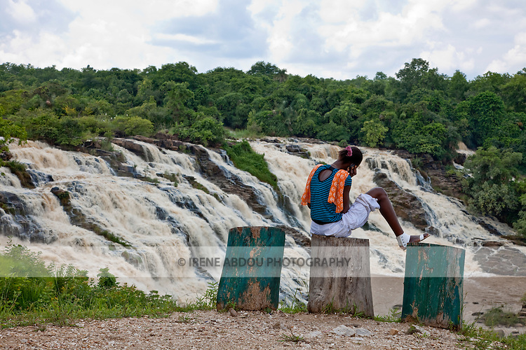 A woman chats on her cell phone while looking over the impressive Gurara Falls.  On the Gurara River in Nigeria's Niger State, the waterfalls are 200 meters wide, boasting a sheer drop of 30 meters.  An approximately 2-hour drive from the capital of Abuja, the falls makes a pleasant day trip and picnic stop from the capital.