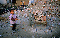 CHINA. Beijing. A young boy amongst the ruins of an old hutong (tradtional homes) destroyed to make may for new developments aimed at modernising the city for the 2008 Summer Olympics. 2005