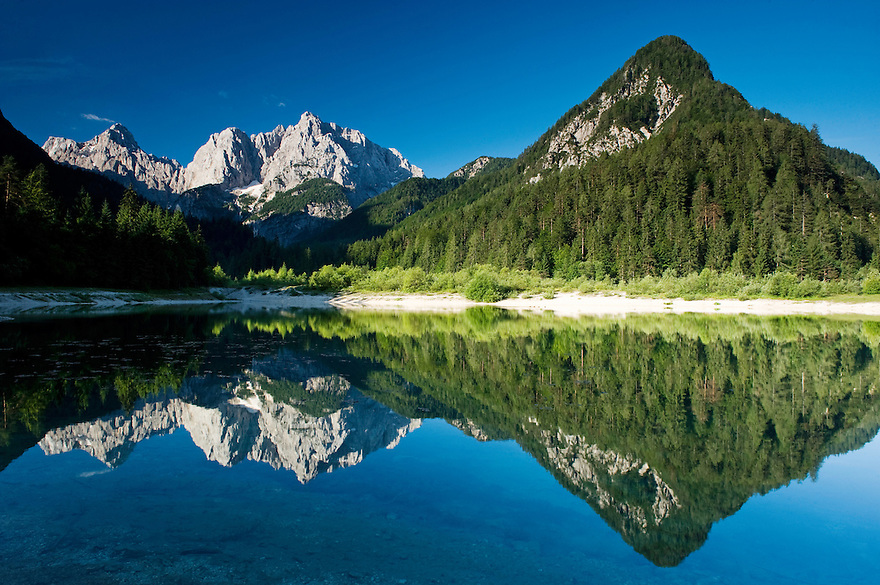 Mount Prisojnik and Mount Razor, reflected in a pond beside the river Pisnica<br /> view from Kranjska Gora<br /> Julian Alps<br /> Triglav National Park, Slovenia<br /> July 2009