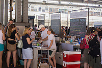 Customers shop at the New Amsterdam Market on South Street in New York on Sunday, June 23, 2013. The market is located in the former Fulton Fish Market with vendors who source their food directly from farmers and producers as well as the farms and makers of artisanal food.  This year because of development of the South Street area the market will only open on one day with the organizers searching for a future permanent home. (© Richard B. Levine)