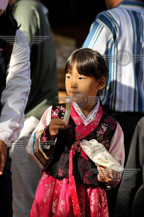 A young girl dressed in traditional costume on a National Public Holiday, in Seoul.