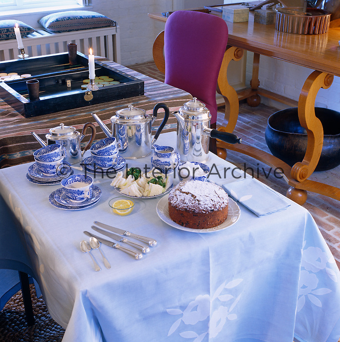 A silver tea service, blue and white cups and saucers and a freshly-baked cake on a small table in the sitting room
