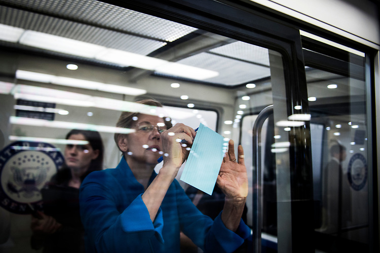 UNITED STATES – July 12: Sen. Elizabeth Warren, D-Mass., writes notes on the Senate Subway as it pulls into the Capitol Thursday July 12, 2018.  (Photo By Sarah Silbiger/CQ Roll Call)