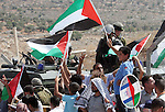 """Palestinian flags are waved in front of israeli soldiers as villagers and peace activist celebrate the decision by the Israeli Supreme Court over the route of the controversial separation barrier being constructed by Israel in the occupied West Bank village of Bilin several kilometers from the city of Ramallah. Israel's Supreme Court ordered the state to re-route a section of its West Bank barrier at the village that has become a potent symbol of Palestinian opposition to the construction. The court ruled that the route of the separation barrier in the Bilin area was """"highly prejudicial"""" to the villagers and demanded that the government map out an alternative route """"within a reasonable period""""."""