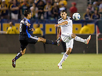 LA Galaxy defender Omar Gonzalez (4) clears a ball away from San Jose Earthquake forward Chris Wondolowski (8). The LA Galaxy and the San Jose Earthquakes played to a 2-2 draw at Home Depot Center stadium in Carson, California on Thursday July 22, 2010.