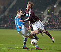 Hearts' Arvydas Novikovas is caught by St Johnstone's Dave Mackay.