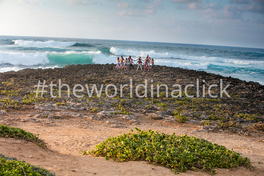 HAWAII, Oahu, North Shore, yoga on the rocks near the ocean at Turtle Bay Resort