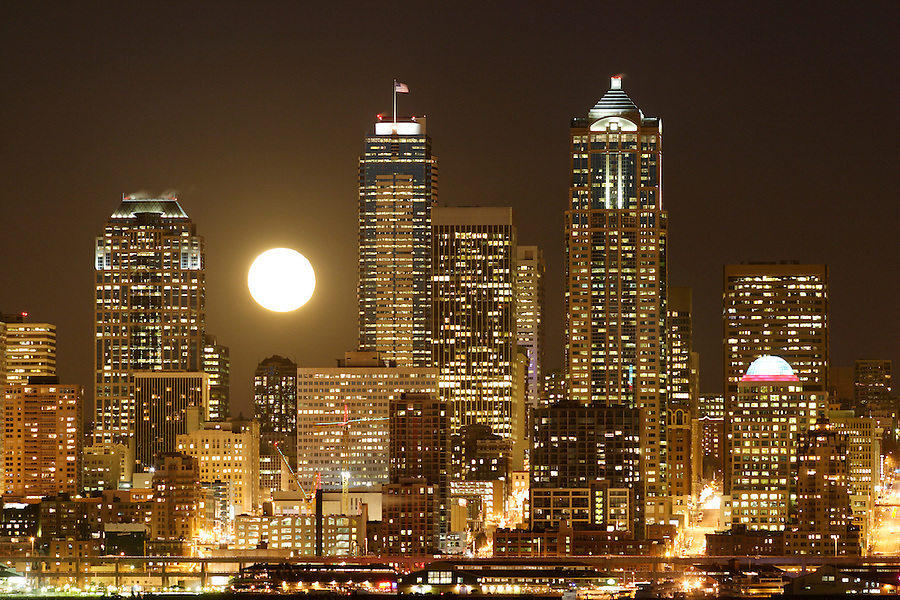 Full moon rising over Seattle city skyline at night, Seattle, Washington, USA