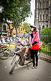 VIETNAM, Hanoi, Young Woman parking her motorcycle outside St. Joseph's Cathedral