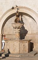 The small fountain of Onofrio, mala Onofijeva fontana, on the loggia loge Luza central square. A woman in white standing by the fountain. Doves. Dubrovnik, old city. Dalmatian Coast, Croatia, Europe.