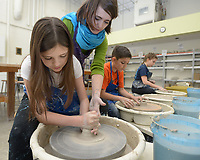 NWA Democrat-Gazette/ANDY SHUPE<br /> Instructor Dani Pugel (top) helps Sadie Skaggs, 12, (left) of Bentonville Wednesday, March 21, 2018, as she creates a clay bowl during the Community Creative Center's Spring Break Pottery Wheel Camp. Students spent the week learning how to make clay items using a pottery wheel.