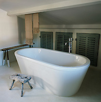 A free-standing bath sits under a low ceiling. A stool and table made from salvaged wood stand nearby and built-in cupboards with louvre doors provide storage.