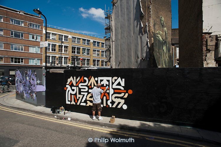 French street artist and rapper Grems paints a mural on a wooden hoarding in Shoreditch, London.
