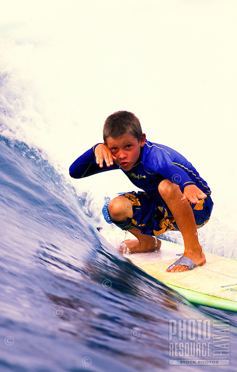 Young boy riding a wave