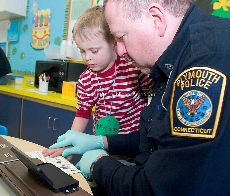 PLYMOUTH, CT- 07 MARCH 07- 030707JT04- <br /> Plymouth Police Officer Kevin Sulek fingerprints Nicholas Ioronimo, 4, at the Terry Nursery School in Plymouth on Wednesday. Sulek was at the school to teach children about safety.<br /> Josalee Thrift Republican-American