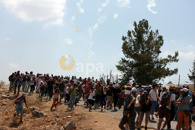 Palestinian and foreign protesters run to cover from tear gas fired by Israeli soldiers during a demonstration against Israel's controversial separation barrier in the West Bank village of Bilin near Ramallah on Aug 14, 2009. Photo by Issam Rimawi