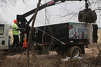 Merced Cervantes, environmental officer, uses a crane to pick up discarded bags of Hydaul-EZ borehole stabilizer, Monday, February 10, 2020 along Logan Cave Rd. in Siloam Springs. Check out nwaonline.com/200211Daily/ for today's photo gallery.<br /> (NWA Democrat-Gazette/Charlie Kaijo)<br /> <br /> A cleanup crew from the Environmental Division for Benton County Government picked up illegally discarded waste products. <br /> <br /> Teresa Sidwell, environmental manager, said a lot of times people are trying to avoid having to pay to take it to the land fill, but added, they have a program where people can drop off large waster products for free.