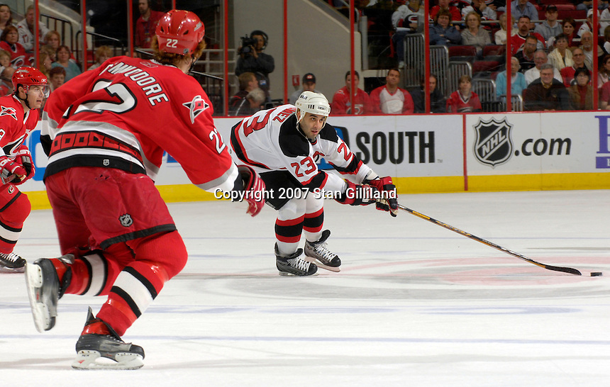 Carolina Hurricanes' defenseman Mike Commodore and teammate Ray Whitney, left, rush to the New Jersey Devils' Scott Gomez as he gathers a puck Thursday, March 15, 2007 at the RBC Center in Raleigh, NC. New Jersey won 3-2.