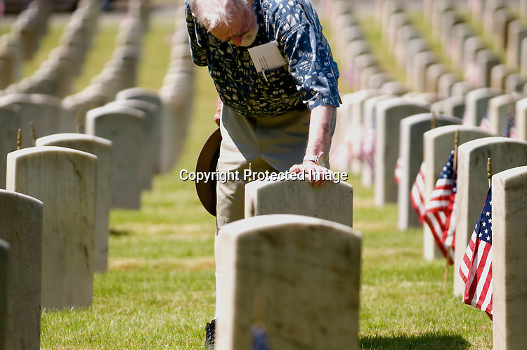 Army veteran James Lumsden puts his hand on his father Daniel's headstone before a Memorial Day ceremony at Washelli Cemetery in Seattle Monday May 25, 2009.