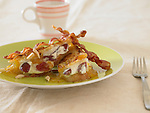 Plate of almond and grape french toast with two slices of bacon and a coffee cup.