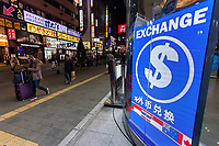 A tourists with suitcases walks past a currency exchange service in Kabukicho, Shinjuku,  Tokyo, Japan. Thursday December 12th 2019
